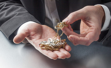 golden and silver jewelery in hands
