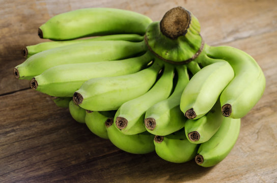 A bunch of bananas on wood table