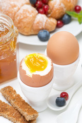 breakfast with eggs, toasts, croissants, fresh berries, close-up