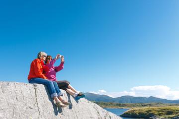 Two women taking photo of Norwegian landscape