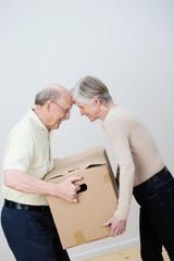 senior ehepaar trägt umzugskarton gemeinsam