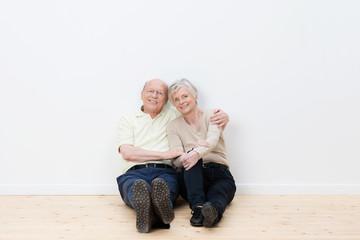 älteres paar lehnt entspannt an der wand