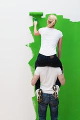 junges paar streicht die wohnung grün