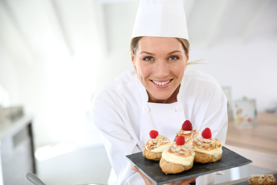 Smiling pastry chef showing desserts on plate