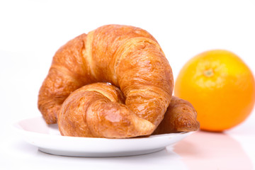Croissants and an orange on the background