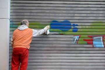 Mann entfernt Graffiti