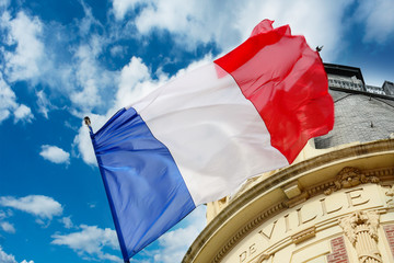 French flag waiving over some Hotel de Ville