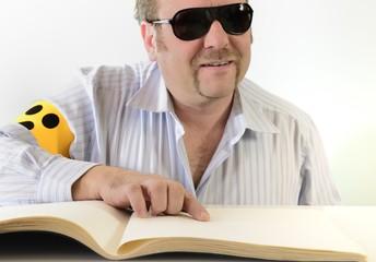 Mann mit Armbinde liest Braille Blindenschrift