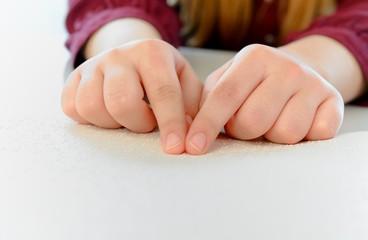 Finger ertasten Blindenschrift