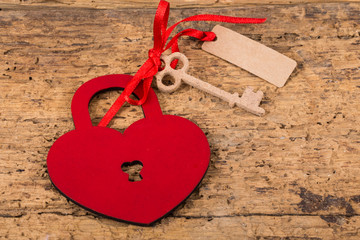 heart shaped lock and key on wooden surface