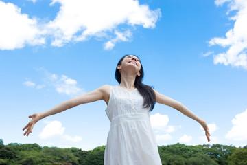 青空に向かって手を広げる女性