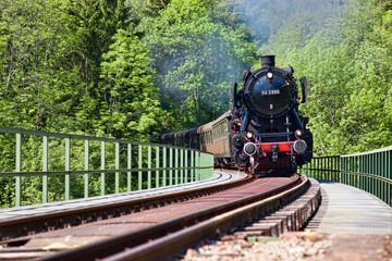 historische Schnellzuglokomotive auf einer Brücke