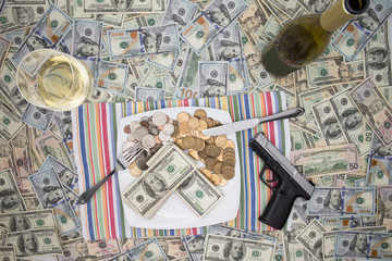 Handgun and champagne on 100 dollar bills