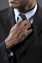 Close up detail of Indian businessman adjusting his tie.