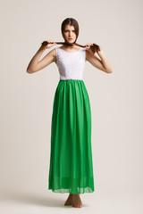 The beautiful young girl in a fashionable dress. Studio. Long ha