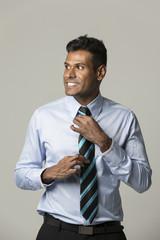 Happy Indian business man adjusting his tie.