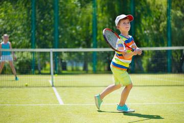 Little boy playing tennis
