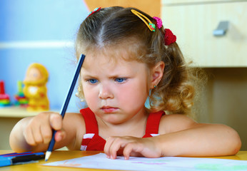 A girl draws with crayons