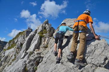 Foto op Aluminium Alpinisme Kinder klettern am Fels im Klettersteig