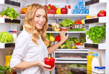 Housewife take red pepper from fridge
