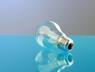 Light bulb isolated on blue glossy background.