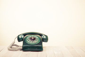 Retro green telephone on wooden table