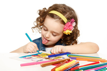 Cheerful little girl with felt-tip pen drawing in kindergarten