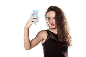 pretty teen girl taking selfies with her smart phone