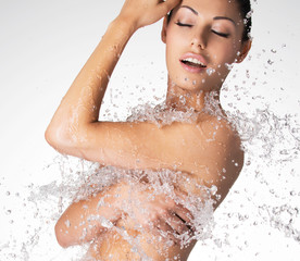 beautiful naked woman with wet body and splashes of water