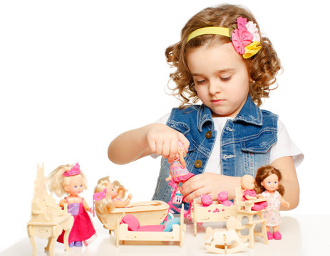 Little girl playing with dolls.