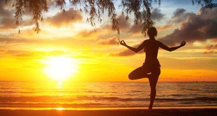 Young woman practicing yoga by the sea at sunset.