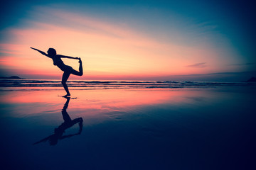 Silhouette of a woman practicing yoga on the beach.