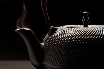 Чугунный чайник с дымком из носика на черном фоне