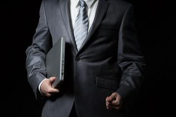 businessman holds laptop