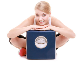 Sporty happy woman with scale, weight loss time for slimming