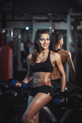 Wall Mural - beauty girl with dumbbells resting in the gym