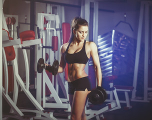 Wall Mural - Sexy girl is training with dumbbells in the gym