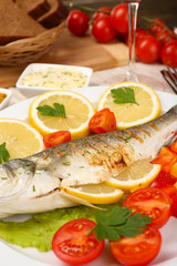 Delicious grilled fish on plate on table close-up