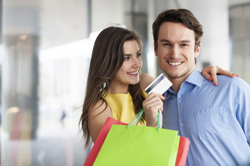 Fashion couple with credit card and shopping bags