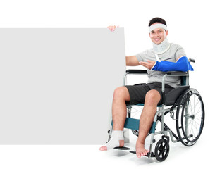 male with broken leg sitting on the wheel chair and presenting t