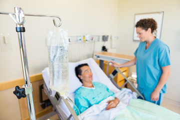IV Bag With Nurse And Patient Looking At Each Other