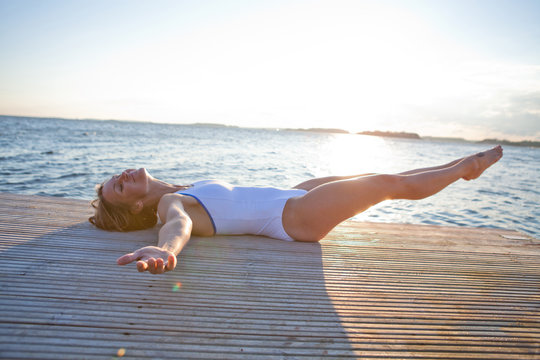 Smiling woman lying on pier