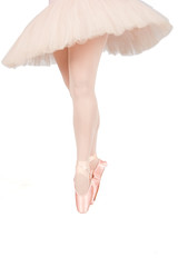 Ballet dancer standing on toes while dancing on white background