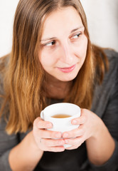 Happy girl in grey holding mug and not looking at camera