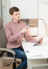 man sitting behind table with tablet and holding imaginary model