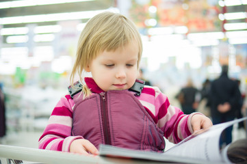 Adorable girl sit on shopping cart and read magazine in supermar