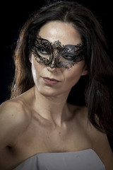 Vintage.Beautiful young woman in mysterious black Venetian mask.
