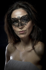 Style.Beautiful young woman in mysterious black Venetian mask. F