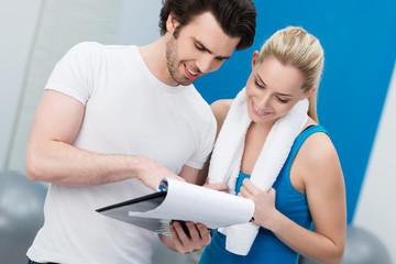 trainer bespricht fitnessplan mit kundin