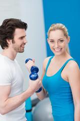 lächelnde frau mit ihrem freund im fitness-center